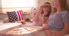 Girl feeding her friend pizza at afternoon pyjama party Stock Footage