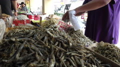 An unknown seller packing up dried anchovies for his buyer. - stock footage