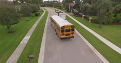 Aerial Following Yellow School bus  passing Nice homes Arkistovideo