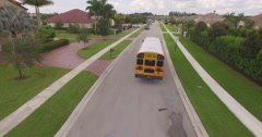 Aerial Following Yellow School Bus in Suburban Neighborhood Arkistovideo