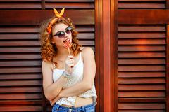 Pin-up girl in sunglasses licking lollipop. Stock Photos