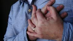 Man clutching chest in pain, CU wide angle Stock Footage