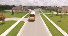 Aerial of Yellow School Bus driving down Suburban Neighborhood 2 Arkistovideo