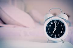 Alarm clock on the bed in bedroom. Stock Photos