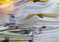 Pile of documents on desk stack up high waiting to be managed. Stock Photos