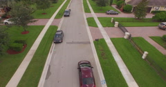 Aerial Flying Down a Suburban street with car driving and Yellow School Bus Stock Footage