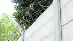 View of the solid wall with barbed wire in the countryside Stock Footage