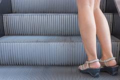 Business woman in high heels standing on escalators stairway Stock Photos