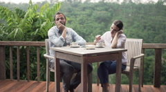 Bored, offended couple drinking coffee by table on terrace Stock Footage