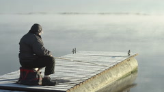 Fog over the water and fisherman on the bridge Stock Footage