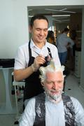 man repaint the hair in a beauty salon - stock photo