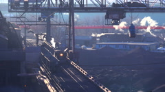 Establishing shot of a busy steel mill with smoke belching suggests global Stock Footage