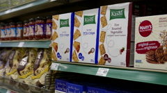 Woman selecting Kashi sea salt pita crisps in grocery store Stock Footage