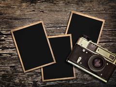 old vintage camera and photos on a wooden background - stock photo