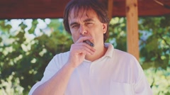 Adult Man is smoking cigar outdoors. Slow Motion 240 fps. - stock footage