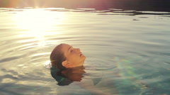 Beautiful Young Woman Relaxing in Swimming Pool at Sunset Stock Footage