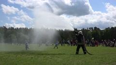 Fireman with hose spray water under cheerful children kids in park. 4K Stock Footage
