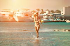Stock Photo of Happiness female running on the beach, yachts background and under sunlight