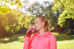 Woman Drinking Water After Exercise at the Park Stock Photos