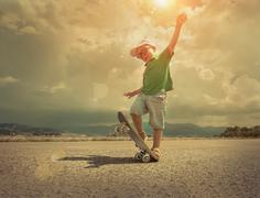 Stock Photo of Child with skateboard under sunlight.