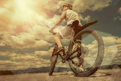 Stock Photo of Man in helmet and glasses stay on the bicycle under sky with clo