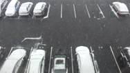 Stock Video Footage of A high angle view of snow falling on a parking lot with cars.
