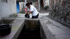 Women taking water from ancient well Stock Footage
