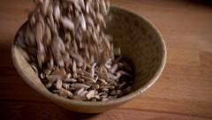 Sunflower seeds falling into dish, slow motion Stock Footage