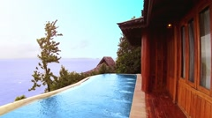 Ocean view villa with pool surrounded by tropical trees - stock footage