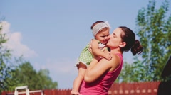 Mother is playing with her baby daughter outdoors. Slow Motion 240 fps. Stock Footage