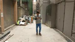 Boy look smart phone screen walk towards narrow passage Stock Footage