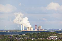 Long distance view over rural landscape to a steaming coal-fired power statio Stock Photos