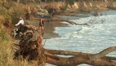 Coastal erosion & rising sea levels - man & dog escape ocean wave Stock Footage