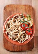 Cooked whole wheat spaghetti in a terracotta bowl - stock photo