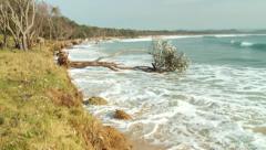Coastal erosion & rising sea levels - follow wave hit and tilt up - stock footage