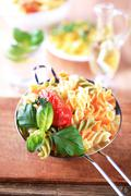 Tricolor corkscrew pasta in a metal sieve Stock Photos