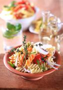 Stock Photo of Tricolor corkscrew pasta in a terracotta bowl