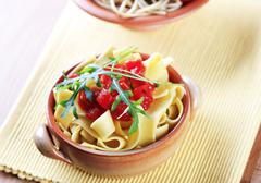 Ribbon pasta and diced tomato topped with arugula - stock photo