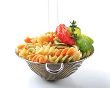 Stock Photo of Tricolor corkscrew pasta in a metal sieve