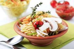 Tricolor corkscrew pasta in a terracotta bowl Stock Photos
