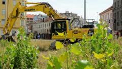 View of the yellow excavator in the grass nearby the city Stock Footage