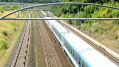 Train passes on the long railway in the countryside - highway in the distance Stock Footage