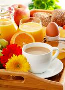 Breakfast on tray served with coffee, orange juice, egg, rolls and honey. Bal - stock photo