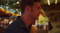 Stock Video Footage of Close up of a couple as they play a carnival game
