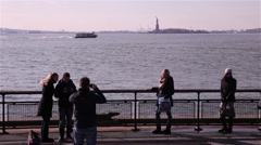 Tourists taking picture with the statue of liberty behind, New York Stock Footage