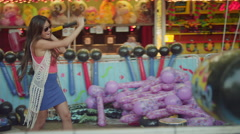 A young woman plays a strength tester at a fair Stock Footage