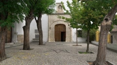 Slow zoom in on old church courtyard with open door. Stock Footage