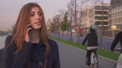 Pretty girl typing on her smartphone walking on embankment of river in city. Stock Footage