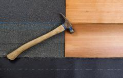 Used roofing hammer with new shingles of composite and cedar wood on felt pap - stock photo