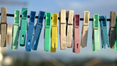 Collection of multicolored clothes pins on a line swaying in the breeze. Stock Footage